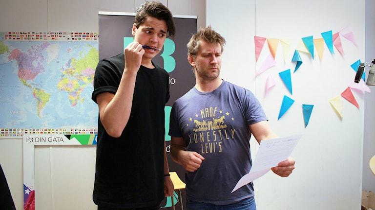 Oscar Zia står och tittar oroligt på Martin från Arbetsförmedlingen, han biter på en penna. Martin Söderberg står och tittar på Oscars personliga brev med en granskande min.