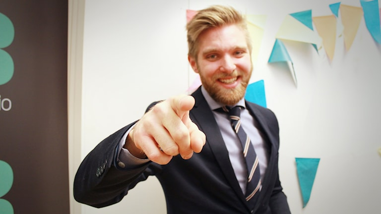 Ted Nilsson pekar mot kameran och lägger på sig sitt bästa säljleende. Han har på sig mörkblå kostym och slips.