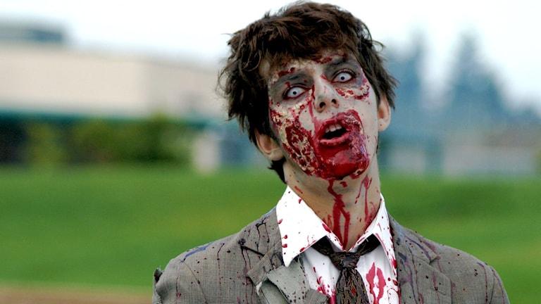 En man i kostym sminkad som en zombie som stirrar in i kameran.