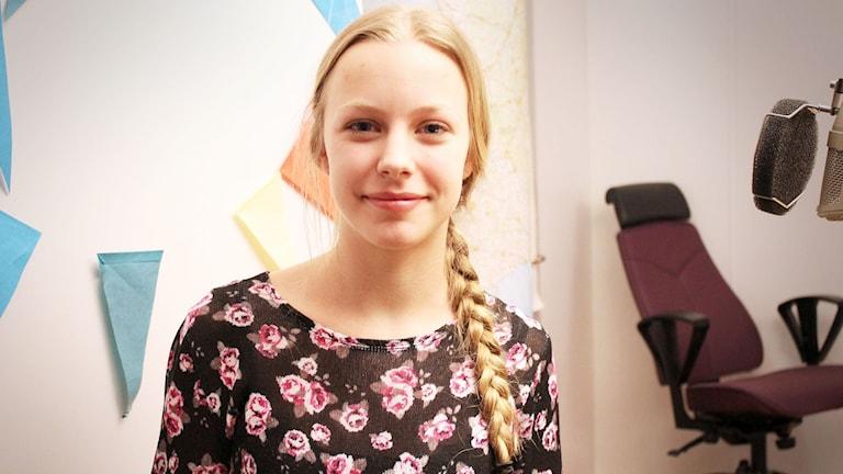 Isabella har blont hår i en lång fläta. Hon tittar in i kameran och ler ett litet leende.