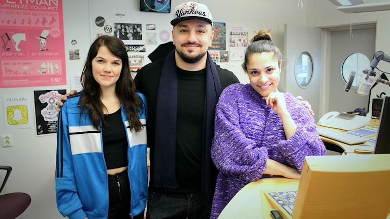 Från vänster till höger: Emma med långt mörkt hår och en blå jacka, Delli med en grå keps, svart tröja och en biffig kropp, och sist Farah med en stor lila kofta. De står på rad och tittar in i kameran.