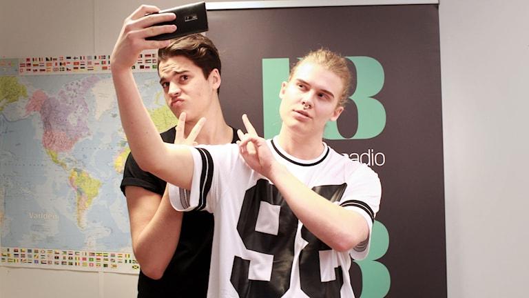 Oscar Zia står i bakgrunden och gör ett v-tecken. Framför honom står vår singel Ian och tar en selfie med mobiltelefonen. Båda två poserar.