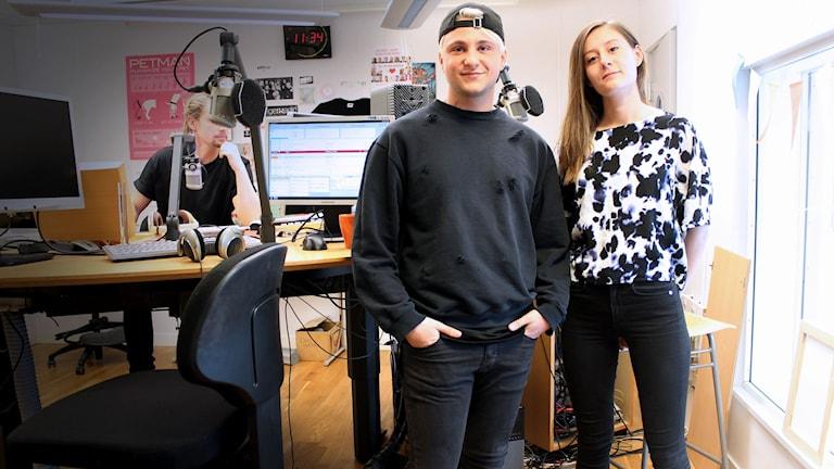 Till vänster står Simon i bakvänd keps och svart tröja. Bredvid står Emilia i en svartvit mönstrad blus med händerna på ryggen. I bakgrunden skymtar producent-Jesper.