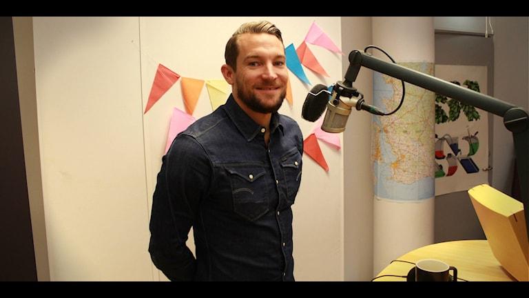 Linus Thörnblad står med händerna på ryggen och tittar in i kameran. Framför honom är en mikrofon.