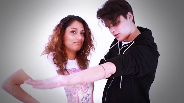 Oscar Zia visar upp den tatuerande ringen som sitter på höger underarm. Farah tittar in i kameran med ett skeptiskt ansiktsuttryck.
