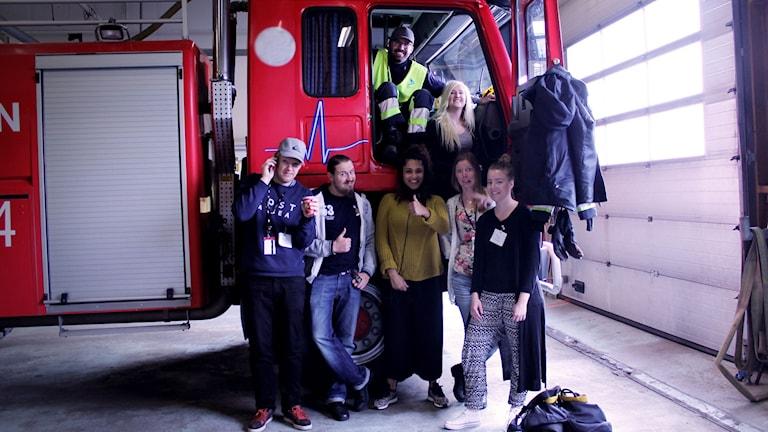 Vi är i branbils-garaget på Göteborg City Airport. Farah står i mitten framför en brandbil med en mikrofon och är omringad av flygplatsens flygbrandmän.