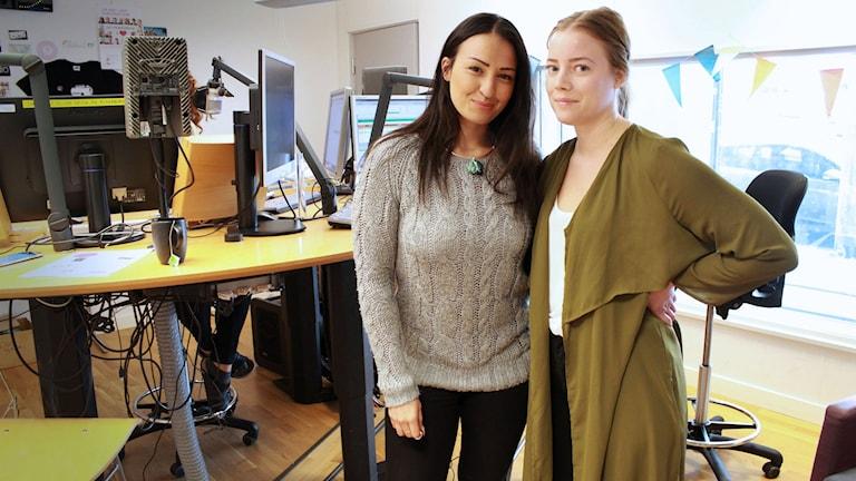 Sanaa och Lisa står tätt bredvid varandra i studion. Sanaa har grå kofta och mörkt, utsläppt hår. Lisa har ljusare uppsatt hår och en grönaktig tröja.