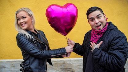 """Isabelle Hambe och Juan Havana håller i en hjärtformad ballong. Det ser ut som att Isabelle ger ballongen till Juan och att han utbrister """"TILL MG!?"""""""