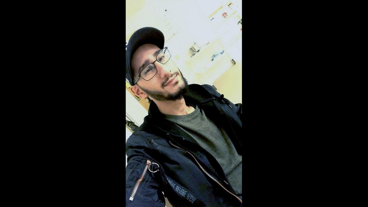 Maher har svarta kläder, glasögon och keps.