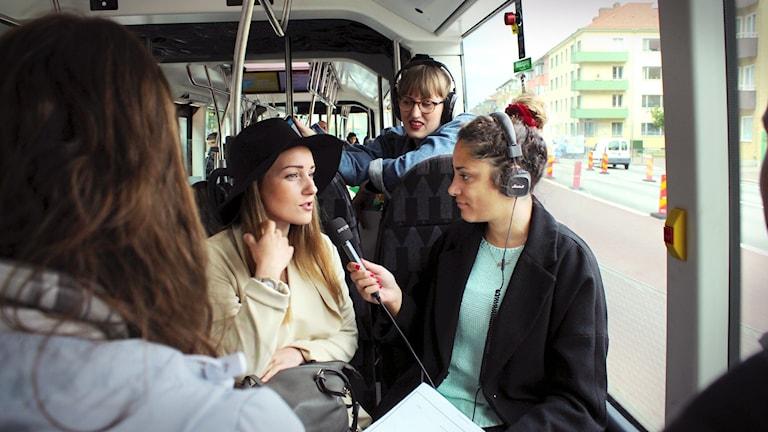 Farah sitter ner i ett fyrsäte och intervjuar Louise med en mikrofon. Louise pillar sig i håret och har på sig en svart hatt. Producent-Sofie tittar upp bakom Farah och tittar på Louise.
