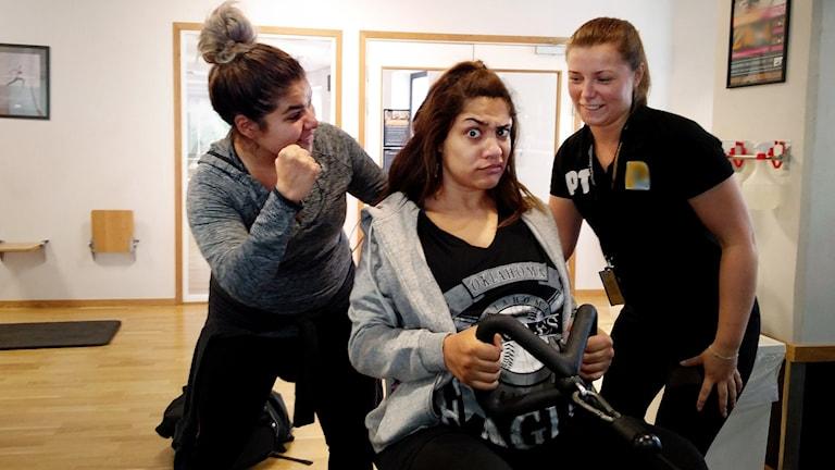 Farah sitter vid en roddmaskin och gör en väldigt skeptisk min samtidigt som hon tittar in i kameran. Bredvid henne står Arantxa och den personliga tränaren Malin och peppar henne.