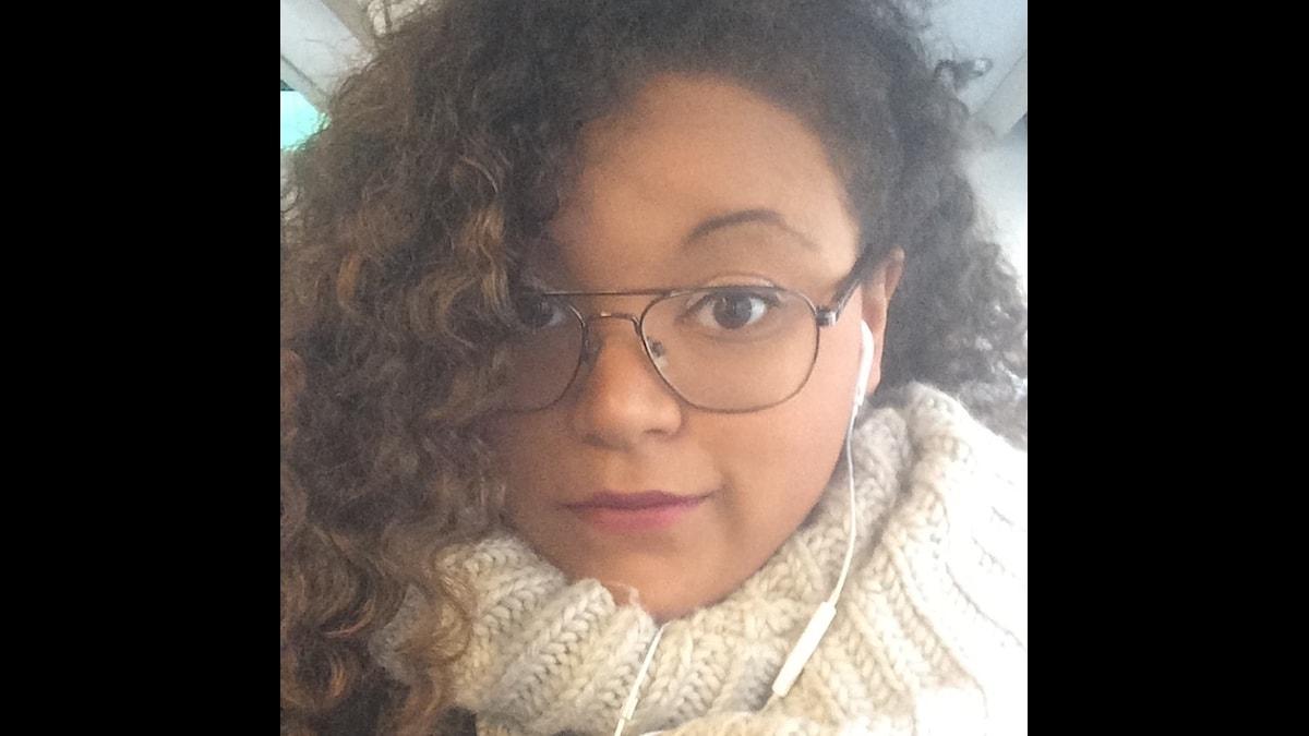 Amanda har glasögon och en vit halsduk på sig.