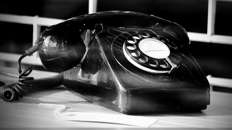 Svartvit bild på en gammaldags telefon med sån skiva man snurrar på och krullig sladd.