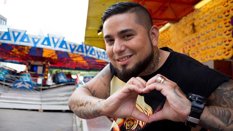 Juan tittar in i kameran och ler. Han håller upp händerna framför sig som ett hjärta.