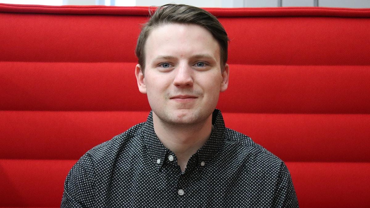 Oskar sitter i en röd soffa och har skjorta på sig.