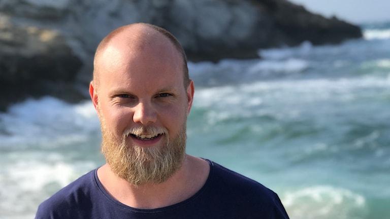 Niklas vid havet och ler.