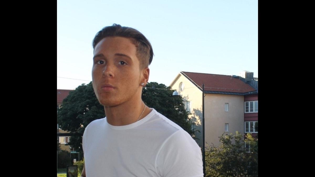 Lenson har vit t-shirt och är utomhus.