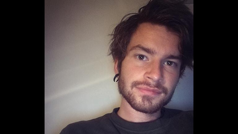 Felix tittar in i kameran med mörka ögon, mjuk skäggstubb och rufsigt hår. Han har en piercing i örat.