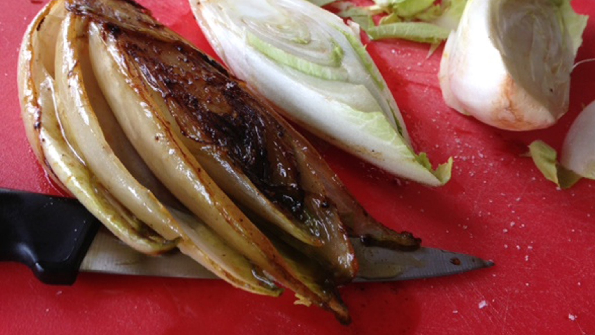 Bild på stekt och ostekt endivesallad på röd skärbräda