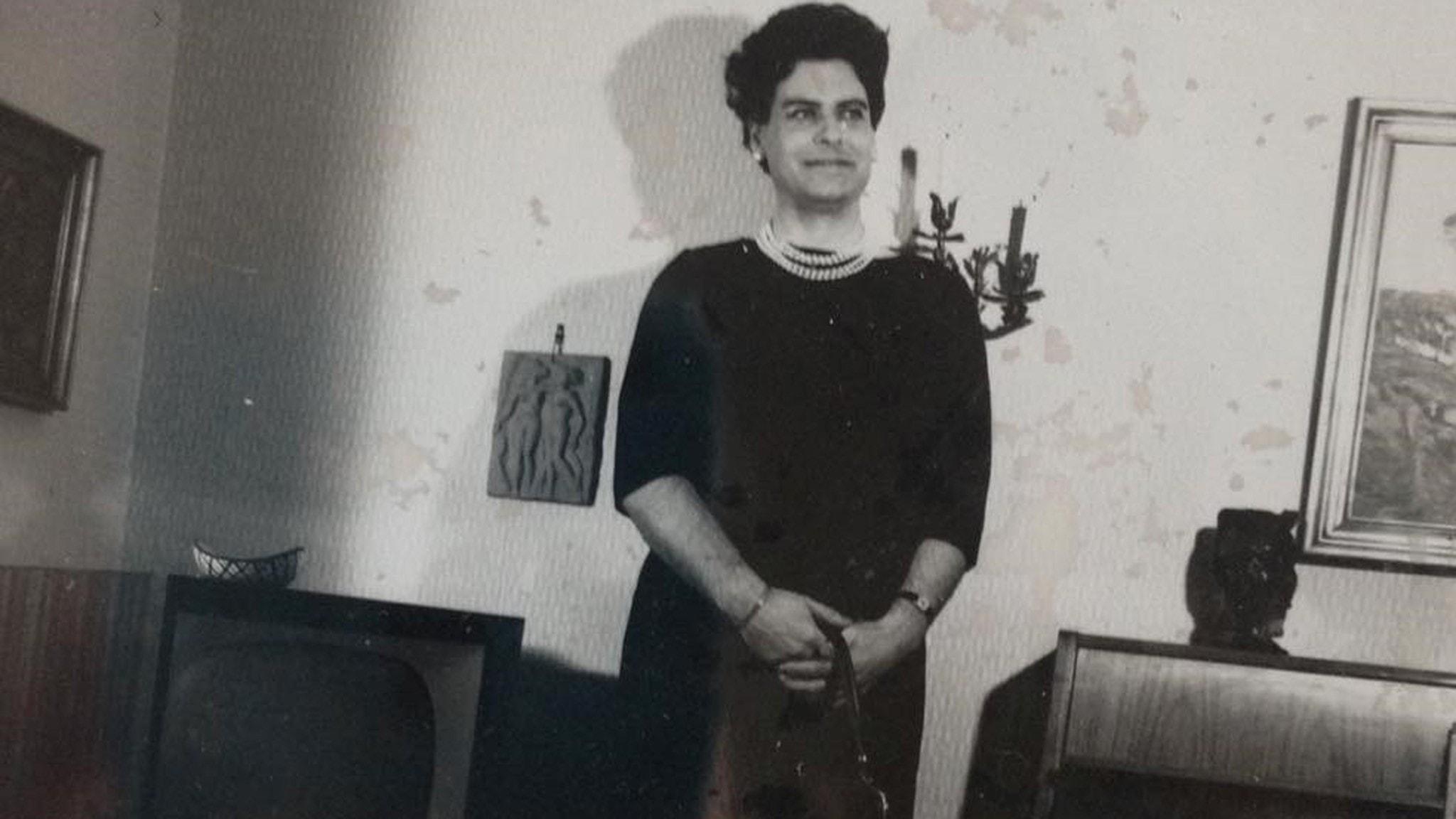 Svartvit bild av Eva-Lisa Bengtson som står i svart klänning med en handväska i handen.