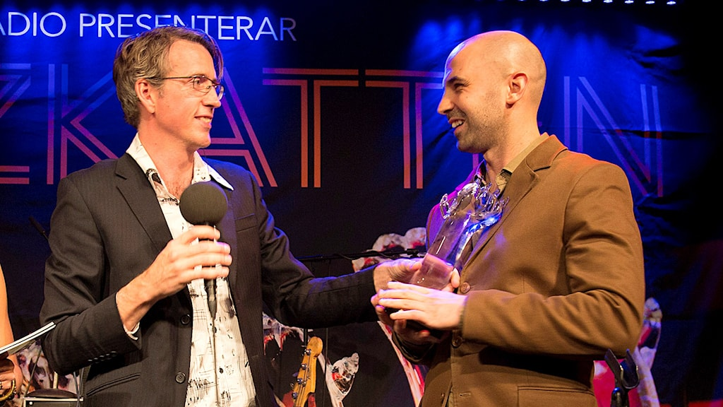 Trummisen Robert Mehmet Sinan Ikiz tar emot priset åt Jacob Karlzon 3 som blev årets grupp på P2 Jazzkatten 2015. Foto: Micke Grönberg/Sveriges Radio