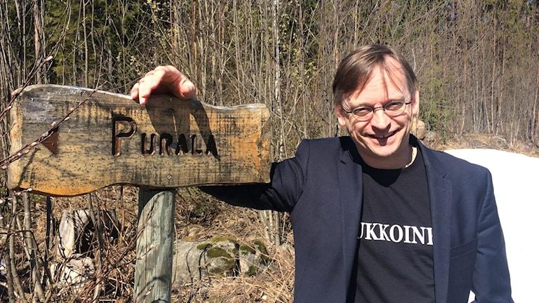 Niclas Persson vid vägskylten till Purala -Finngården. Foto: Virpi Inkeri/SR