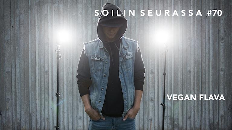 Vegan Flava seisoo kädet taskussa kahden kirkkaan lampun välissä, kasvot jäävät hupun varjoon.