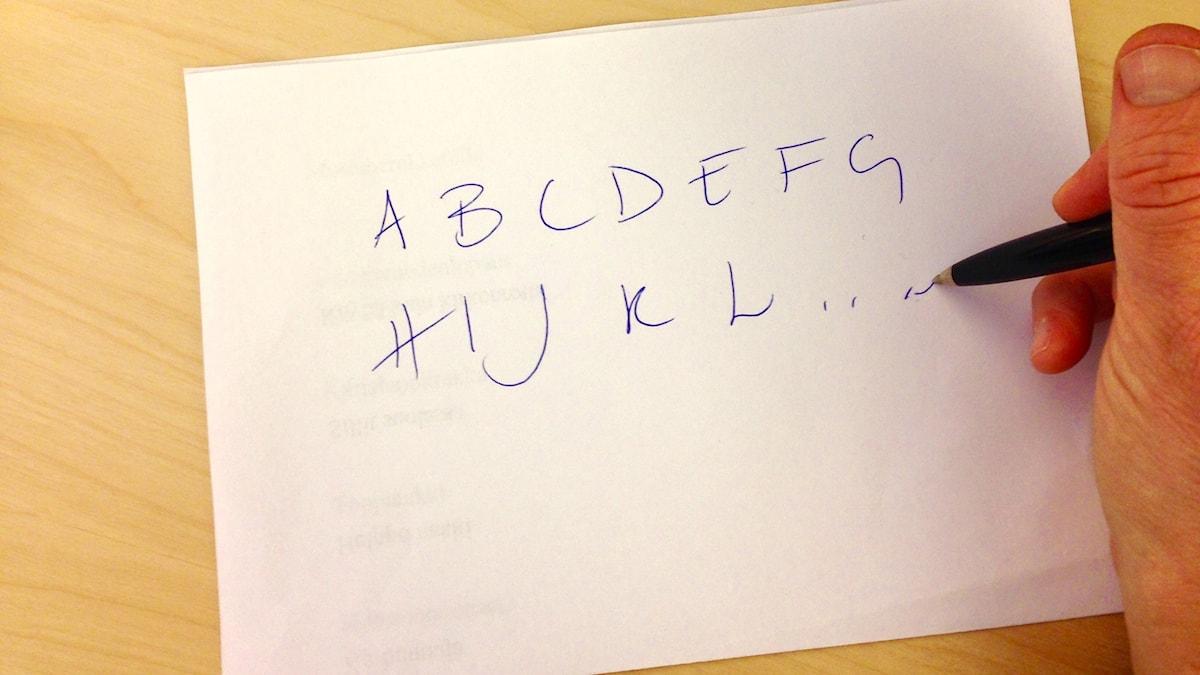 Käsi kirjoittaa kirjaimia paperille.