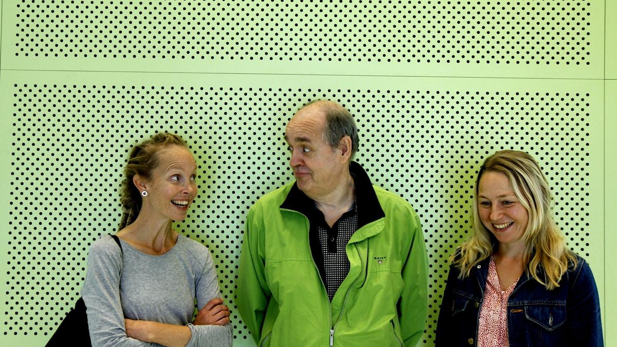 Lukupiiriläiset Hanna Hallakumpu, Keijo Knutas ja Anna Pilvinen seisovat naureskellen vihreän seinän edessä. Keijolla on myös vihreä takki päällä.