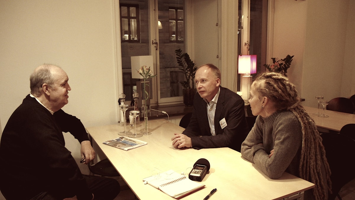 Lukupiiriläiset Keijo Knutas ja Hanna Hallakumpu istuvat pöydän ääressä kirjailija Kalle Kniivilän kanssa.