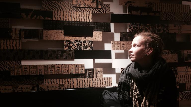 Hanna Hallakumpu mietiskelee seinään nojaten