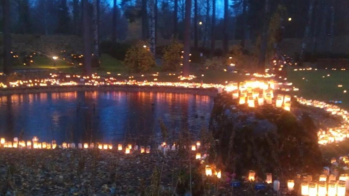 Pimeässä illassa lampea ympäröivät sadat kynttilät, jotka heijastuvat vedestä.