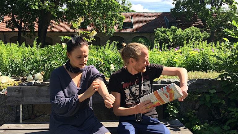 Juontajat Anni Riit'aho ja Timo Laine lätkivät hyttysiä ja raapivat pistoja puistonpenkillä.