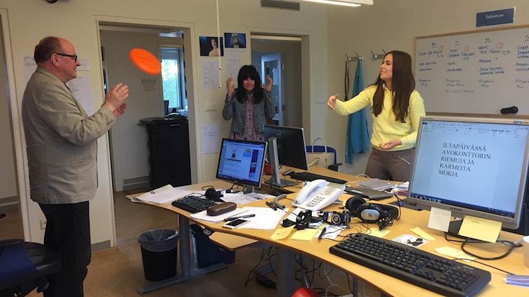 Jorma Ikäheimo ja Marika Pietilä heittävät frisbeetä avokonttorissa.