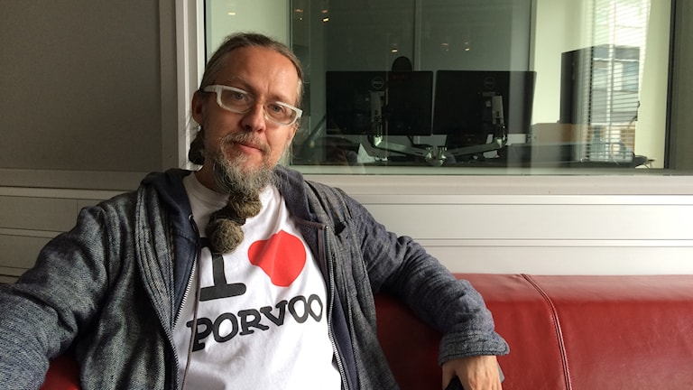 """Henrik Nilsson istuu punaisella sohvalla studiossa yllään paita, jossa lukee """"I <3 Porvoo"""""""