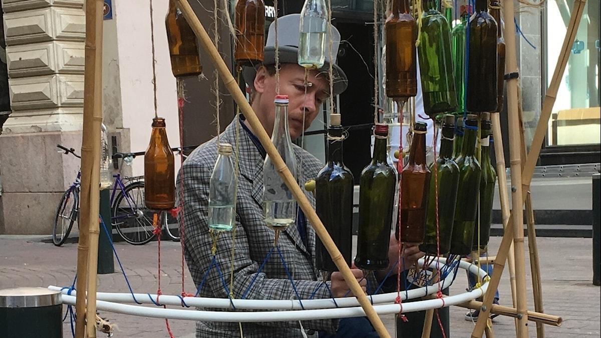 Silinteripäinen mies soittaa pulloja keskittyneesti
