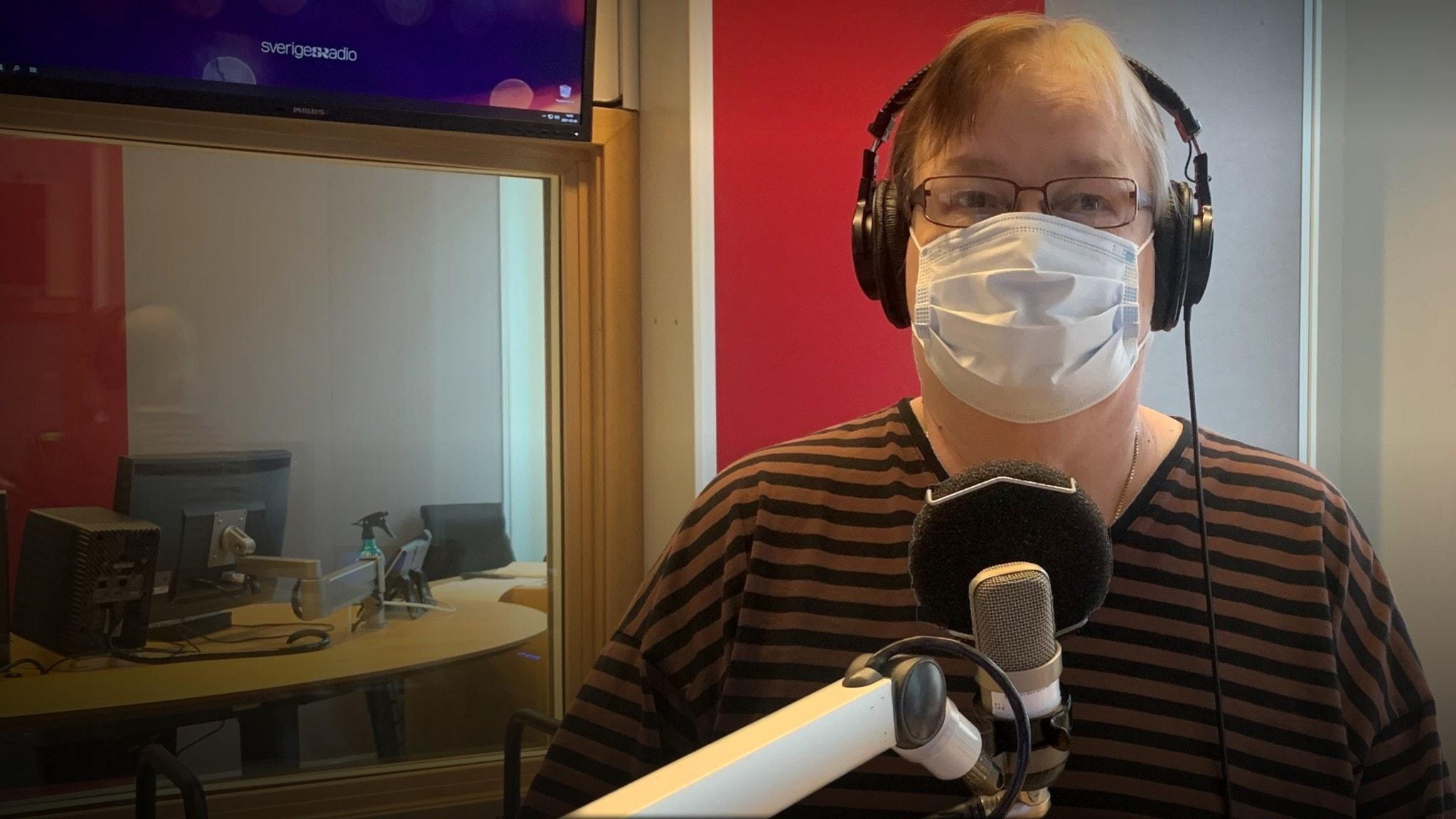 Pirjo Rajalakso seisoo radiostuidiossa mikrofonin takan, kasvomaski päällä.