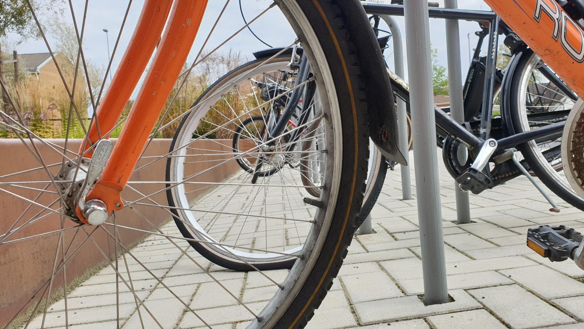 Närbild på cyklar vid cykelställ.