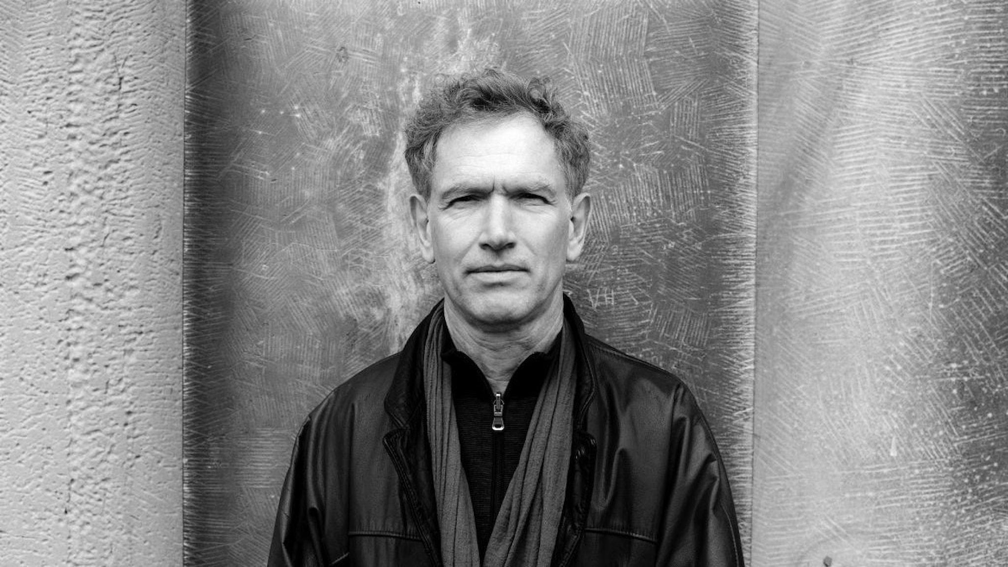 Tonsättaren Hans Abrahamsen i svartvitt står mot en vägg med en halsduk om halsen.