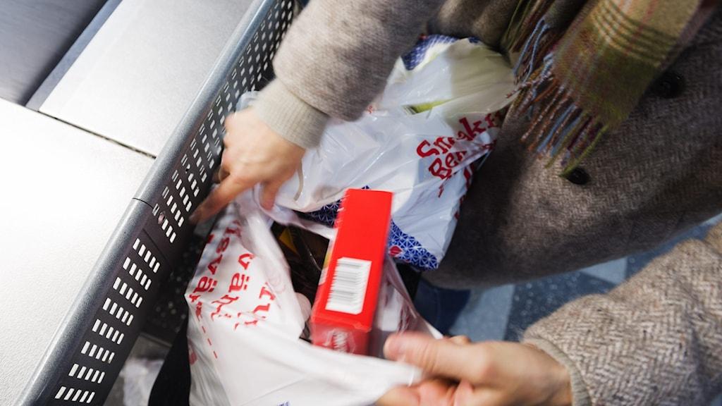 En person som packar matvaror i en påse.