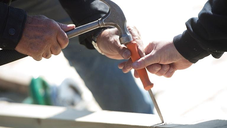 En snickare hamrar ut en kil med hjälp av hammare och en kniv