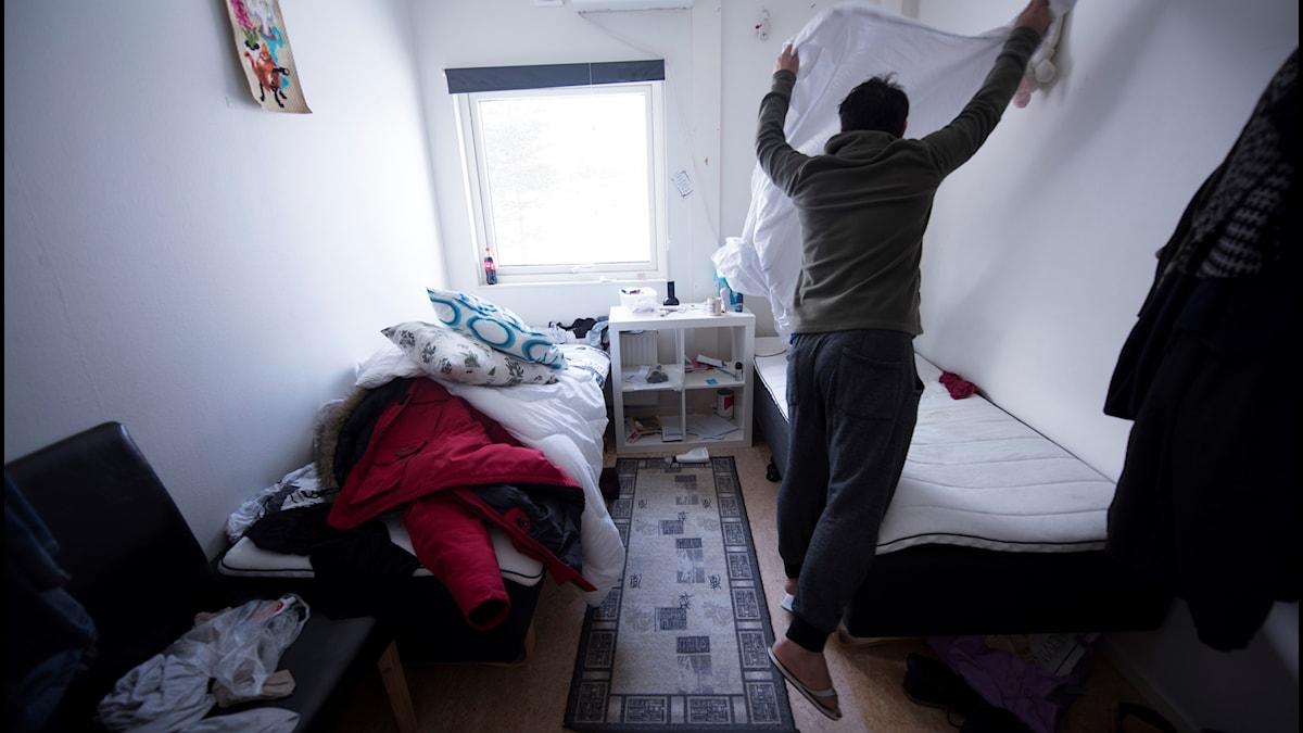 En asylsökande ung man bäddar sin säng på ett  flyktingboende i Pajala.