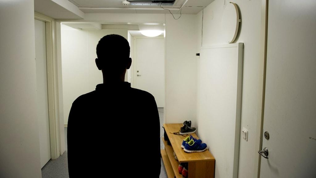Silhuetten av en person på ett asylboende.