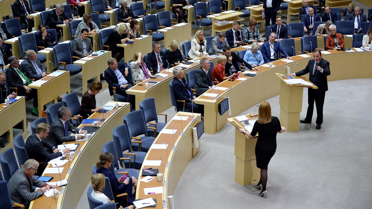 Centerns Annie Lööf och statsminister Stefan Löfven i talarstolen i riksdagen under onsdagens partiledardebatt.