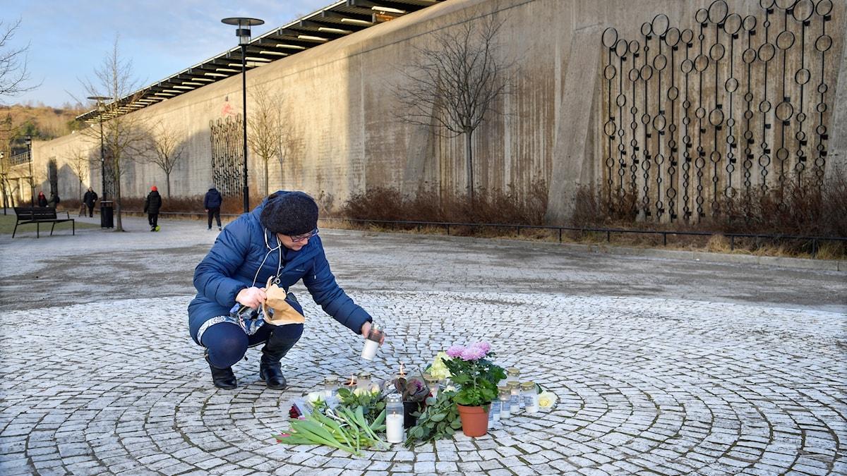 Människor har lagt blommor och tänt ljus på torget i Vårby gård för att hedra den 60-årige man som avled efter en misstänkt handgranatexplosion
