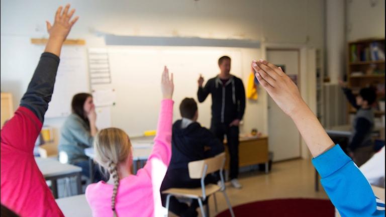 Elever i fjärde klass räcker upp händerna när en lärare undervisar i ämnet svenska