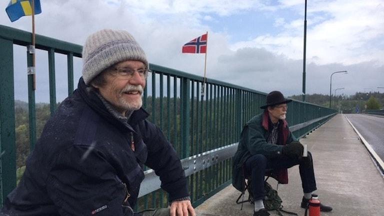 Två bröder sitter på sina pallar på Svinesundsbron. Den ena har en svensk flagga bakom sig, den andra en norsk. Det är enäggstvillingarna Pontus och Ola berglund som träffas varje lördag på bron, eftersom de bor i Norge respektive Sverige men ändå vill träffas varje vecka.