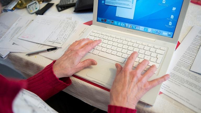 En kvinnlig pensionär sitter vid en bärbar dator och skriver.