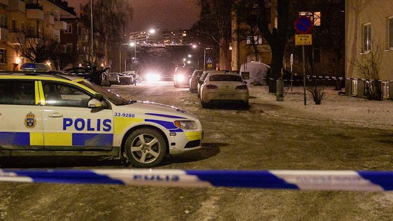 En polisbil och avspärrningsband på en gata.