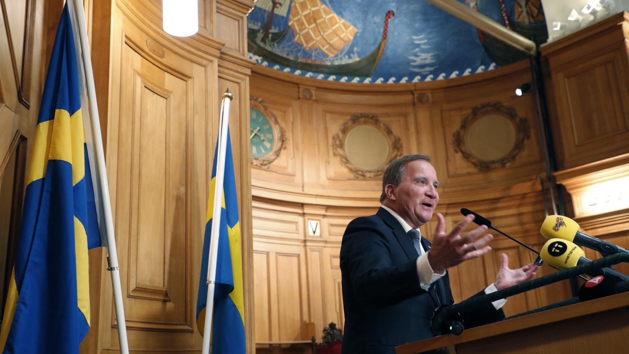 Bild på Stefan Löfven som håller en presskonferens.